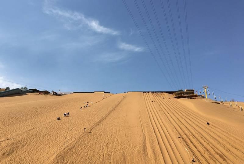 """其北,包兰铁路蜿蜒穿沙行,翠茏沙岭,沙漠奇观""""金沙鸣钟""""之下,园林滴翠"""